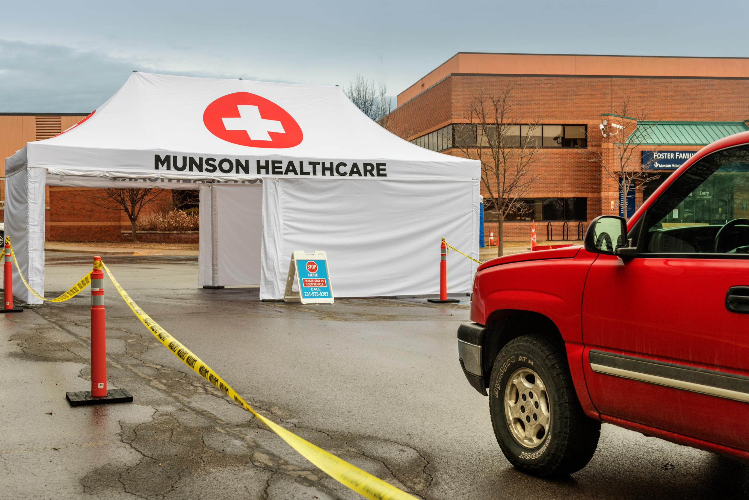 A custom-printed screening-tent being used to check for coronavirus symptoms at Munson Medical Center