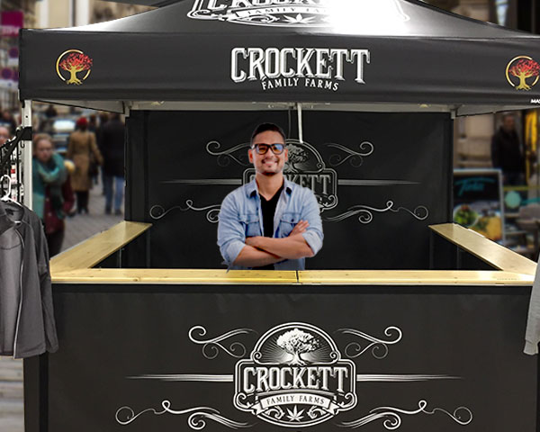 man standing behind counter of custom-printed, black, crocket farms pop up tent