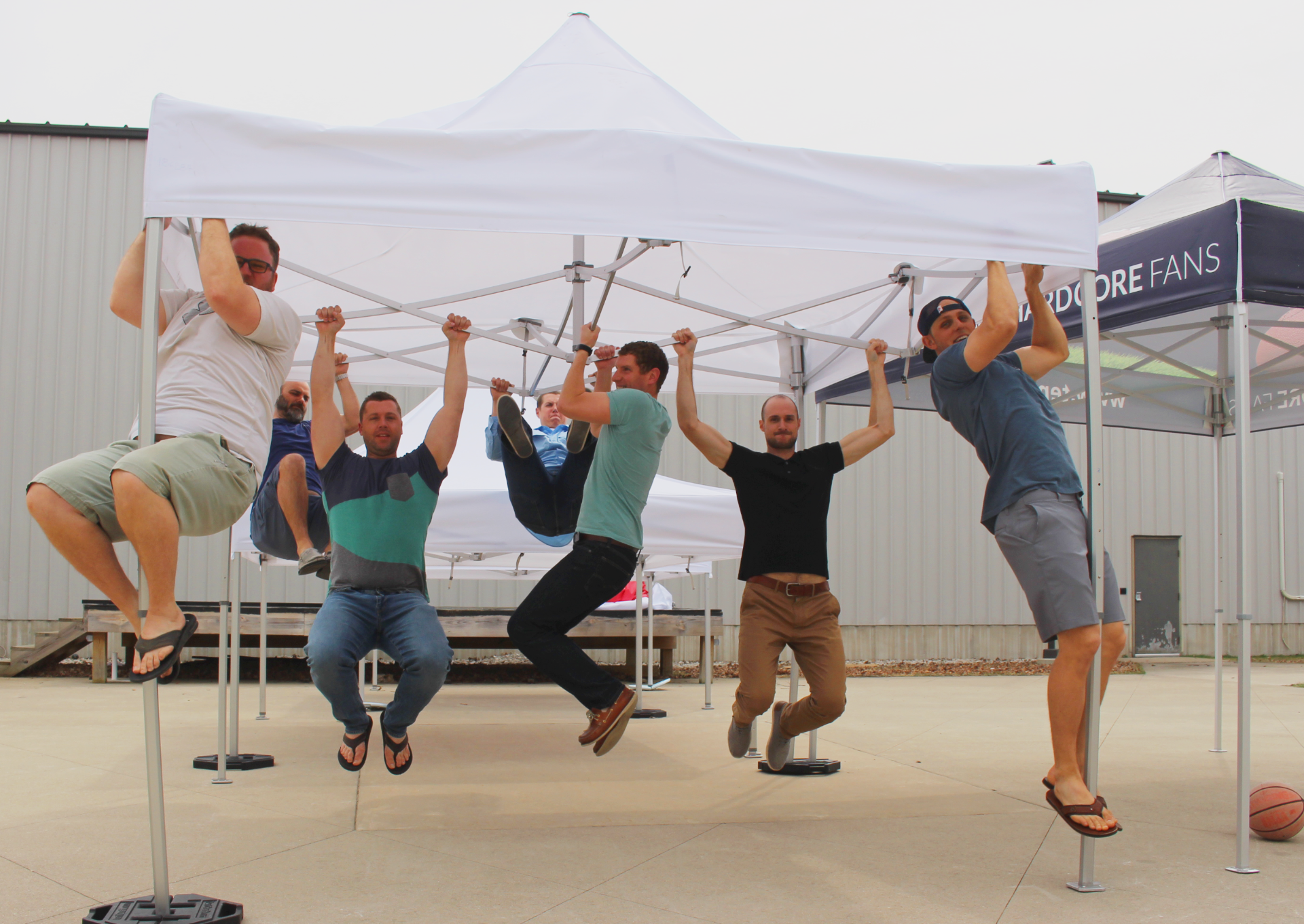 a bunch of guys hanging on a white canopy tent