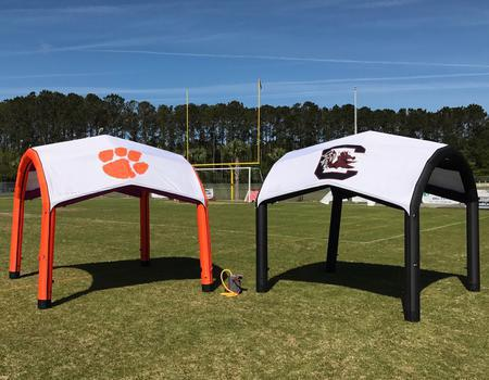 Two college branded Nitrox AIRFRAME inflatable tents at football field.