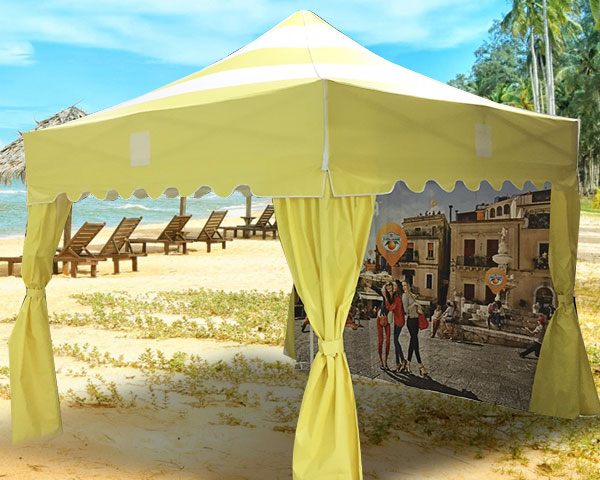Yellow scalloped valance on pop-up tent at the beach.