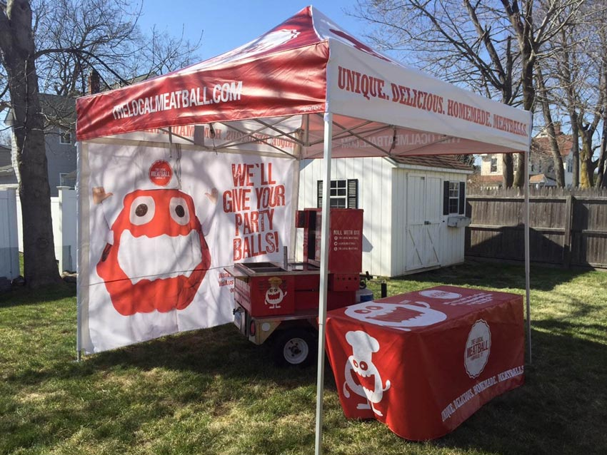 A white and red heavy-duty pop-up tent printed with custom back walls and table cover to match branding.